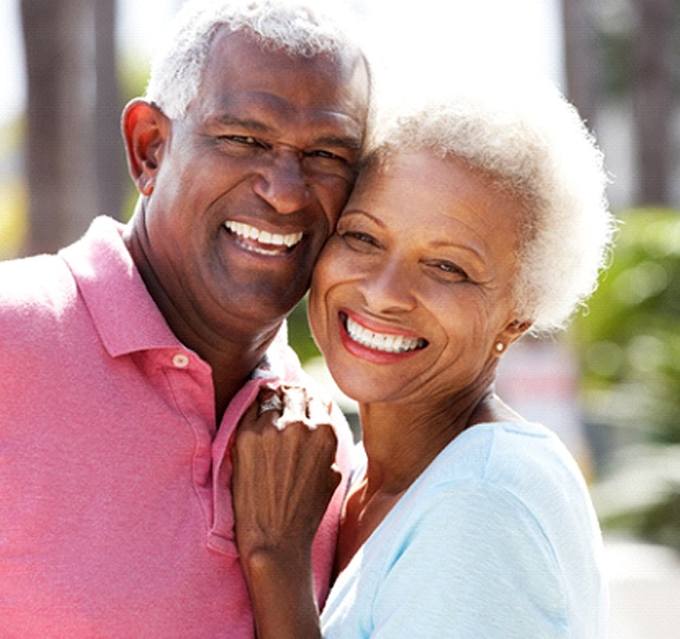 Senior couple leaning and smiling with multiple dental implants in Jacksonville, FL