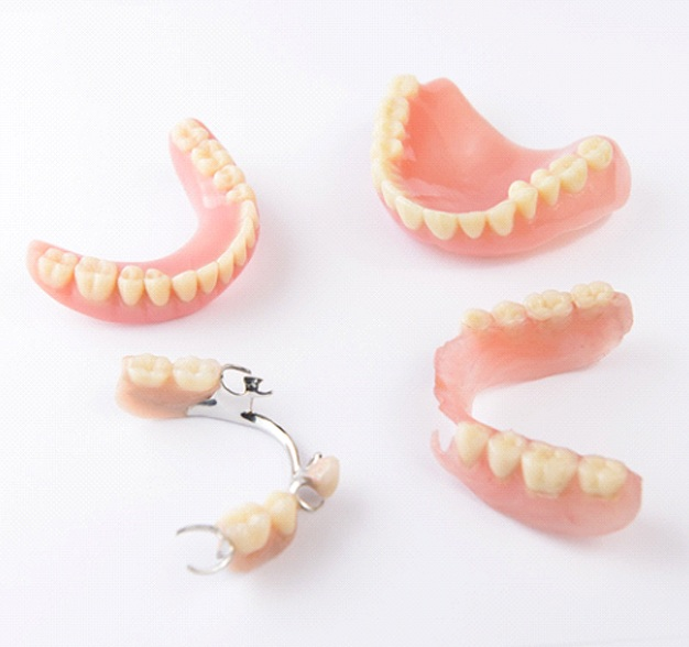 Full dentures and partial dentures on white table