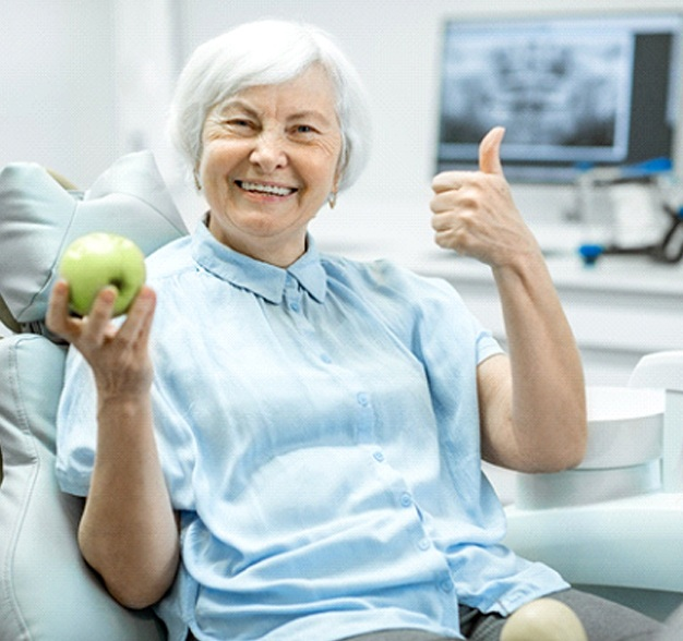 Senior woman in dental chair smiling and holding an apple