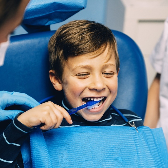 Child practicing tooth brushing during children's dentistry visit