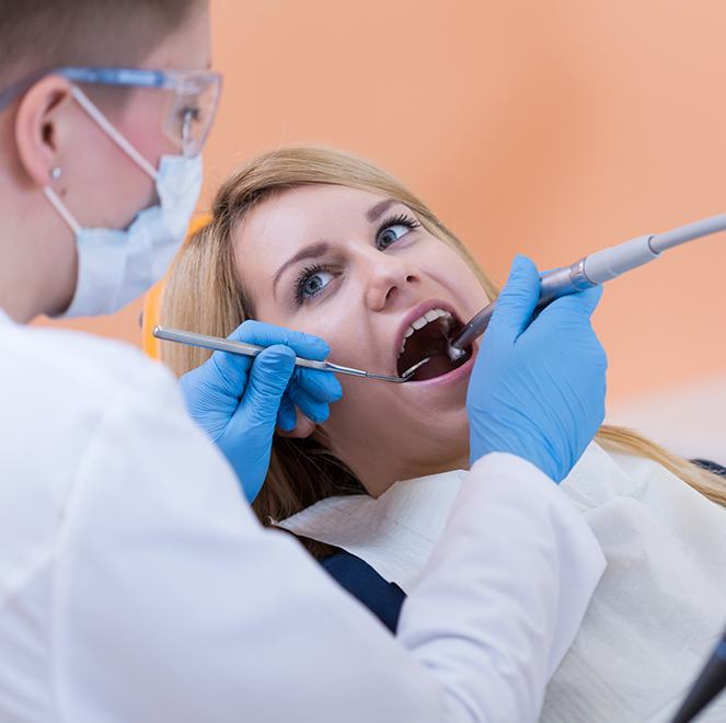 Dentist checking patient's dental sealants