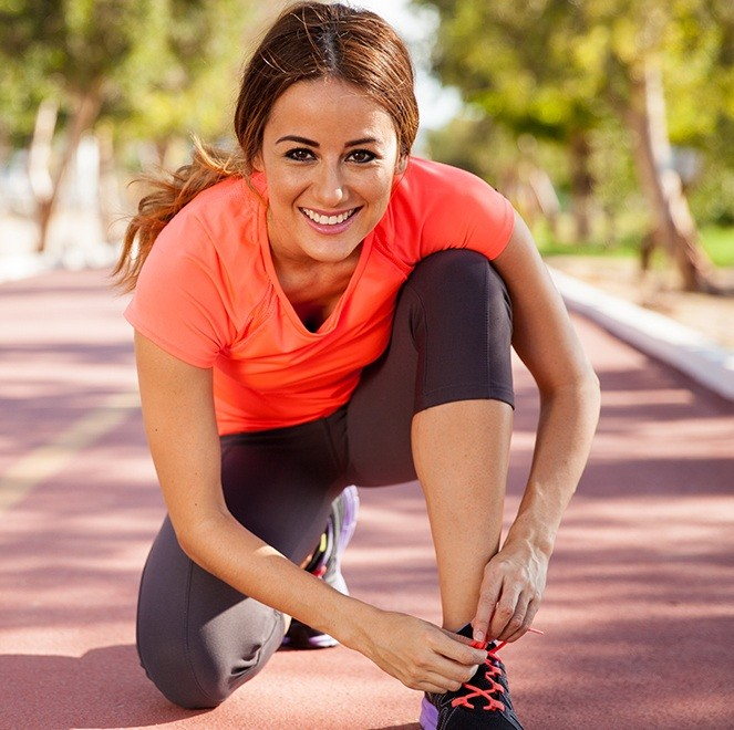 Smiling woman stretching for a run