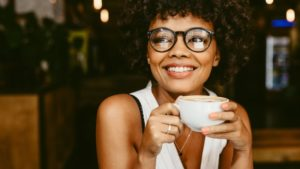 smiling woman sipping a cup of coffee