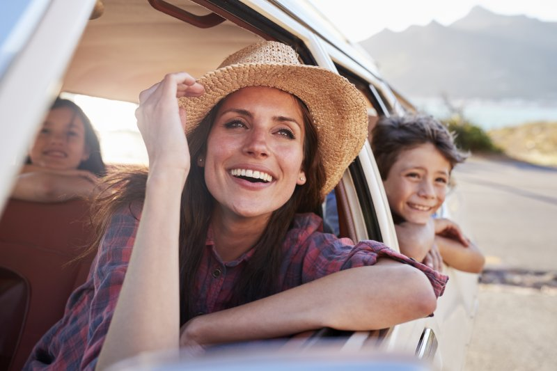 woman smiling in car with porcelain veneers